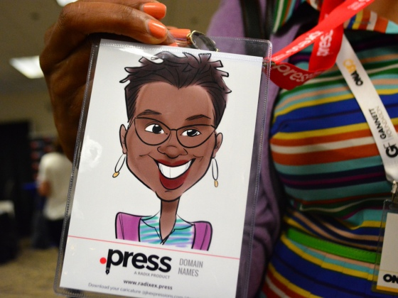 Debra Bass holds up a caricature drawn by Radix' Julia Kelly at the Online News Association Career Fair on Friday, September 25, 2015. (Photo by Nathalie Dortonne/ONA Student Newsroom)